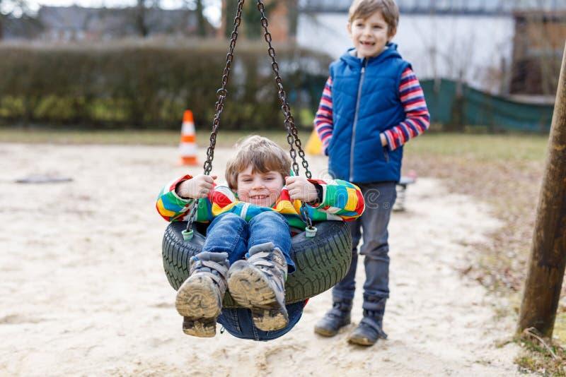 Dos muchachos del niño que se divierten con el oscilación de cadena en patio al aire libre fotos de archivo libres de regalías