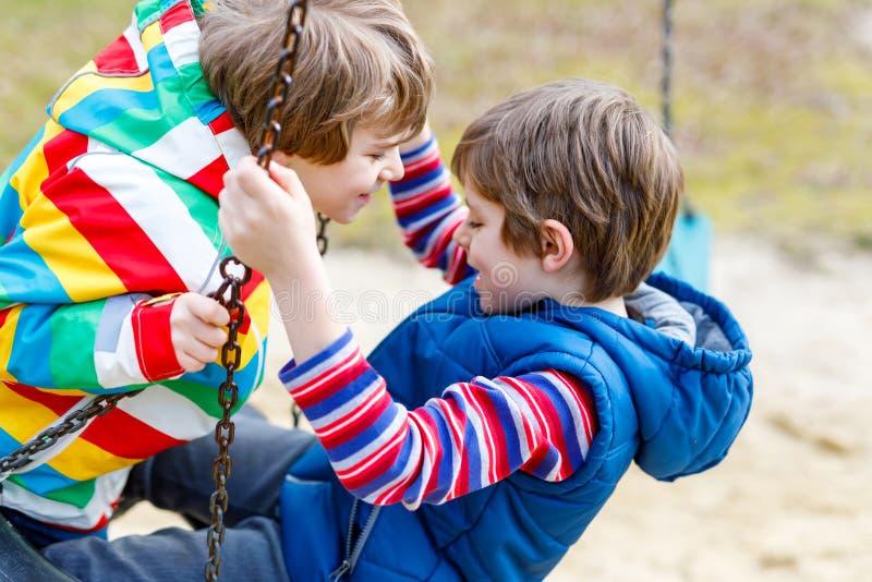 Dos muchachos del niño que se divierten con el oscilación de cadena en patio al aire libre imagen de archivo