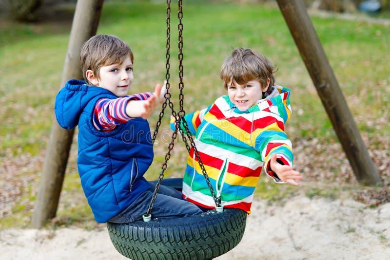 Dos muchachos del niño que se divierten con el oscilación de cadena en patio al aire libre fotografía de archivo