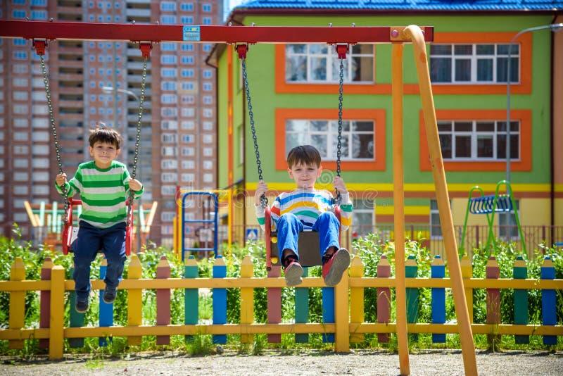 Dos muchachos del ni?o que se divierten con el oscilaci?n en patio al aire libre Ni?os, mejores amigos y hermanos balanceando en  fotografía de archivo