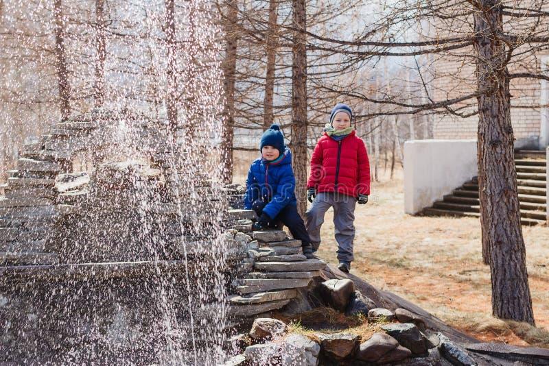 Dos muchachos del preescolar jugar en una pequeña fuente en el parque en primavera temprana niños en ropa caliente fotos de archivo libres de regalías