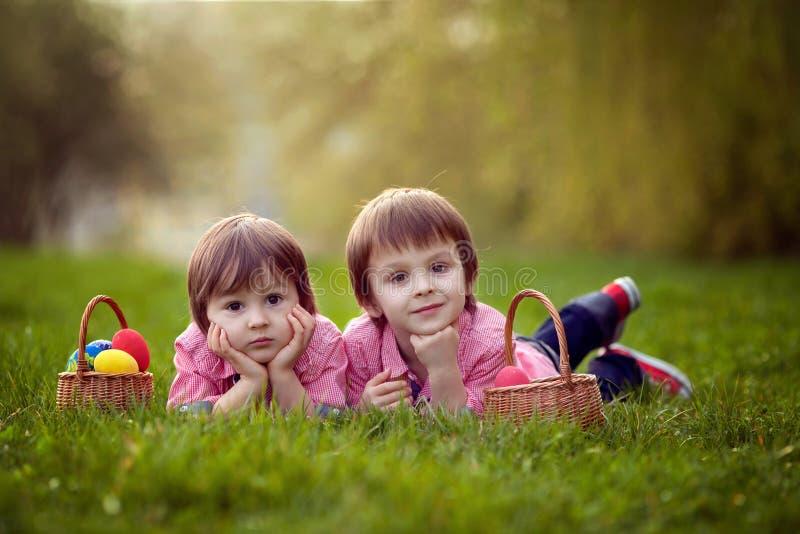 Dos muchachos en el parque, divirtiéndose con los huevos coloreados imágenes de archivo libres de regalías