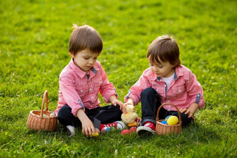 Dos muchachos en el parque, divirtiéndose con los huevos coloreados imagen de archivo libre de regalías