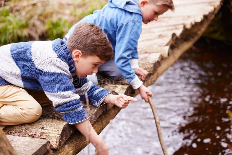 Dos muchachos en el puente de madera que juega con los palillos en corriente imagenes de archivo