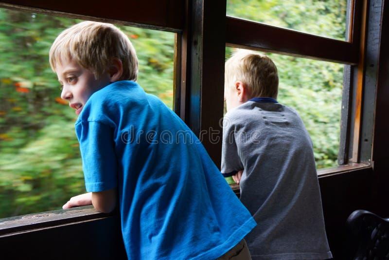Dos muchachos en el tren que mira hacia fuera la ventana fotos de archivo