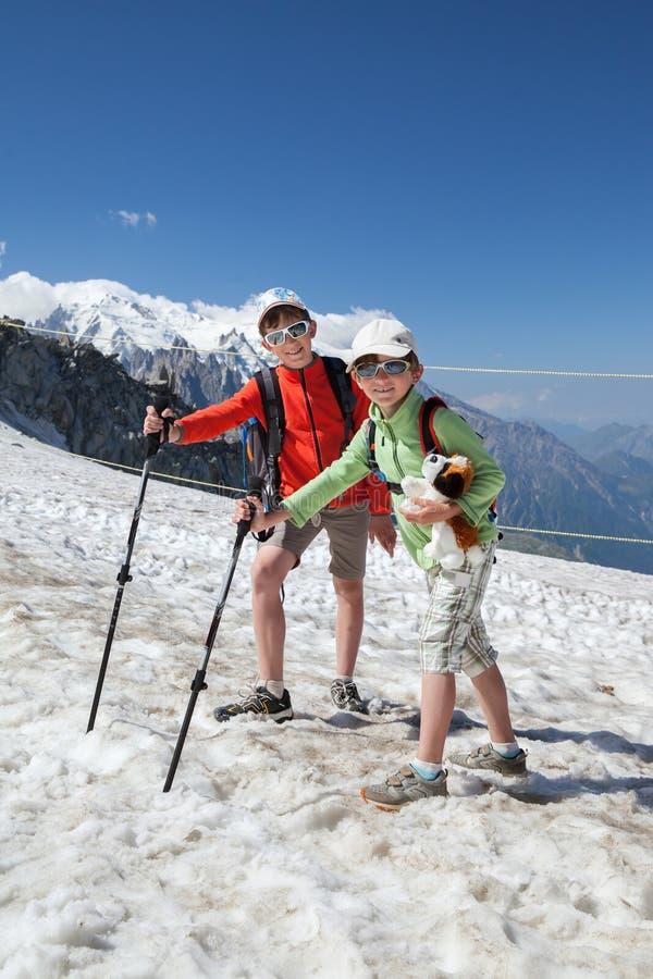 Dos muchachos están caminando en la demostración en montañas imagen de archivo