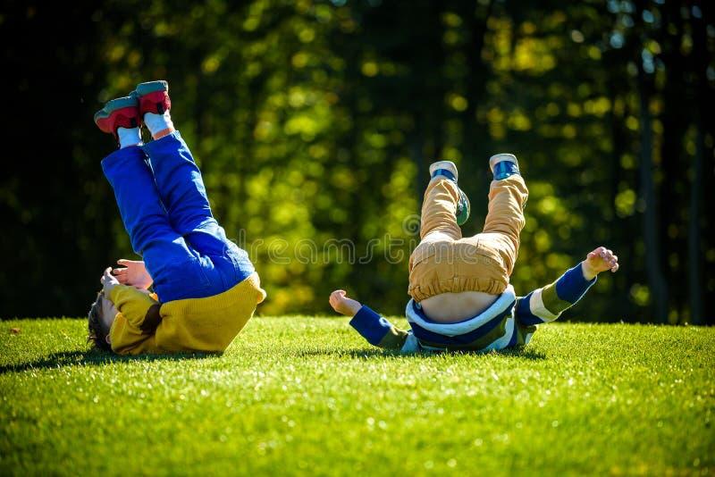 Dos muchachos felices que juegan en prado fresco de la hierba verde La caída y la sonrisa juntas los niños de los hermanos son me imagen de archivo