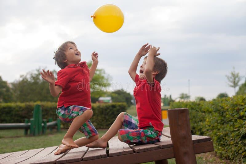 Dos muchachos, hermanos, jugando con el globo amarillo en el parque imagenes de archivo