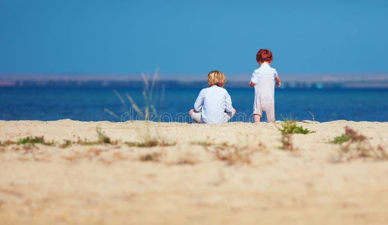 Dos muchachos, hermanos que se sientan en la playa arenosa por la mañana cerca del lago foto de archivo libre de regalías