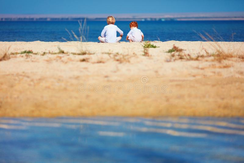 Dos muchachos, hermanos que se sientan en la playa arenosa por la mañana cerca del lago fotos de archivo libres de regalías