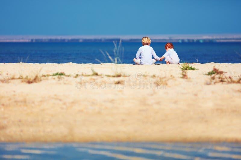 Dos muchachos, hermanos que se sientan en la playa arenosa por la mañana en el lago costean imagen de archivo