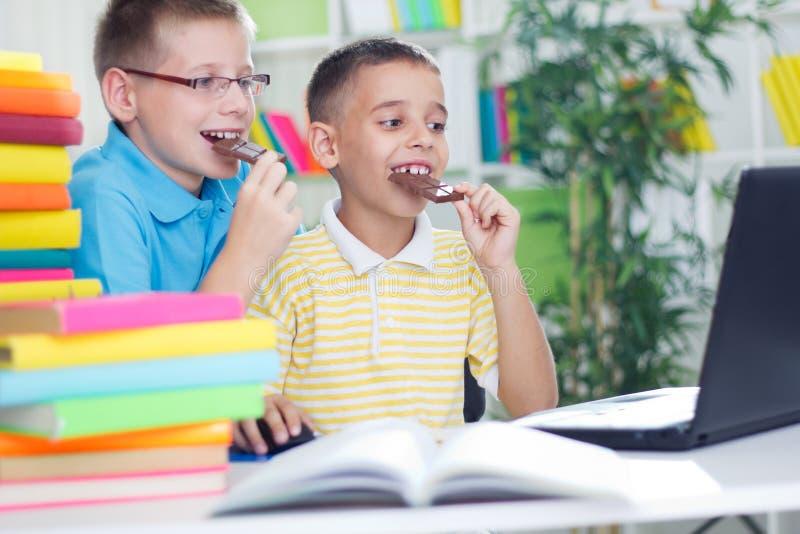 Dos muchachos jovenes que comen el chocolate y que usan el ordenador portátil fotos de archivo