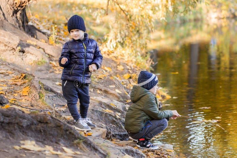 Dos muchachos jovenes que juegan la pesca con los palillos cerca de la charca en parque de la caída Pequeños hermanos que se divi foto de archivo