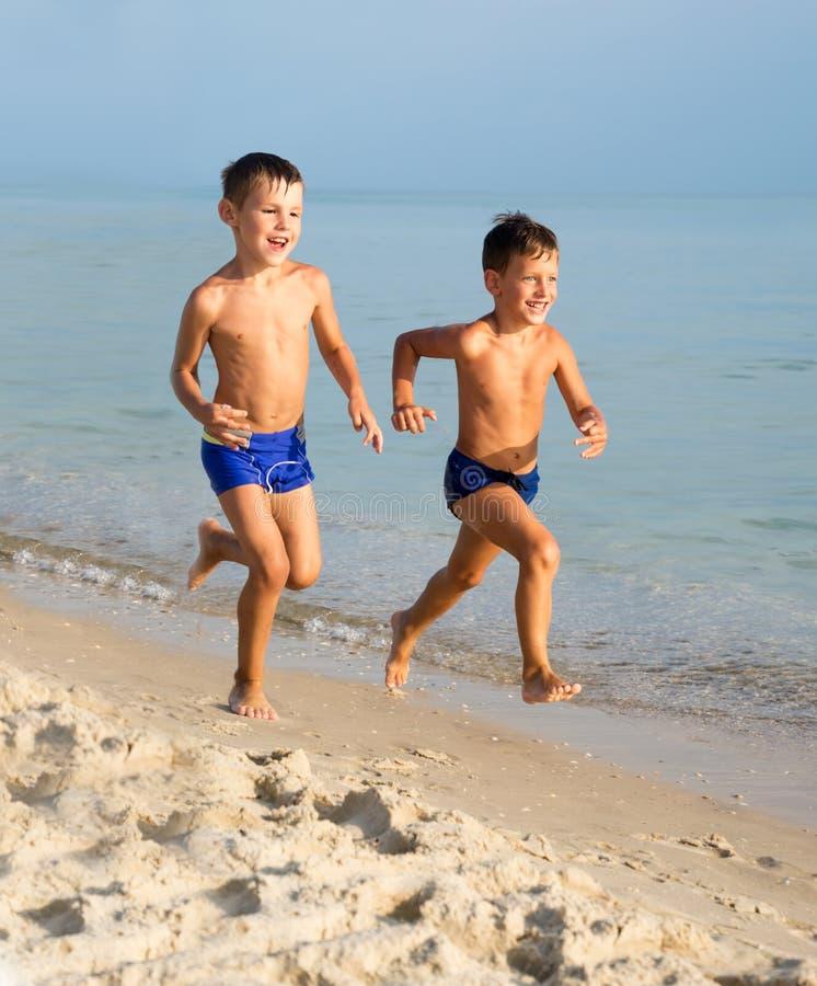 Dos muchachos jovenes que se divierten en la playa imagenes de archivo