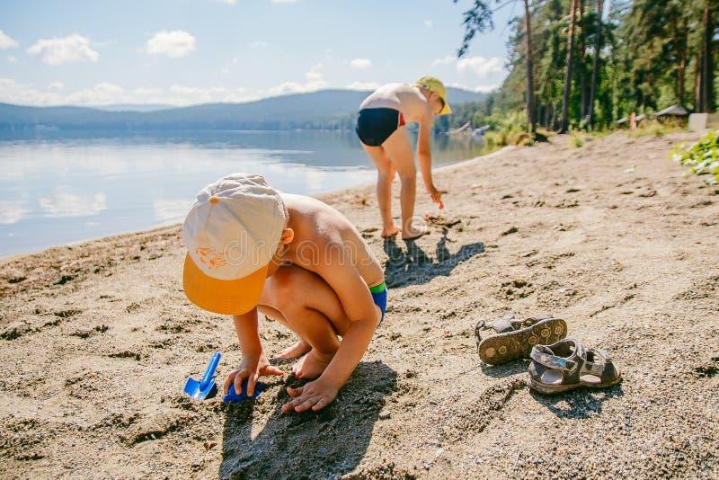 Dos muchachos juegan en la arena en la playa del lago imagen de archivo libre de regalías