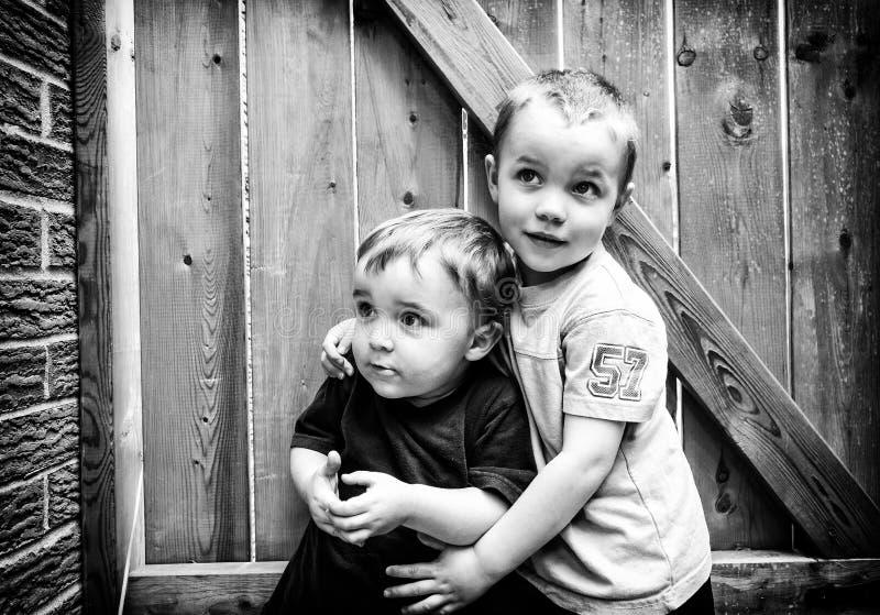 Dos muchachos junto que parecen para arriba - blancos y negros fotografía de archivo libre de regalías
