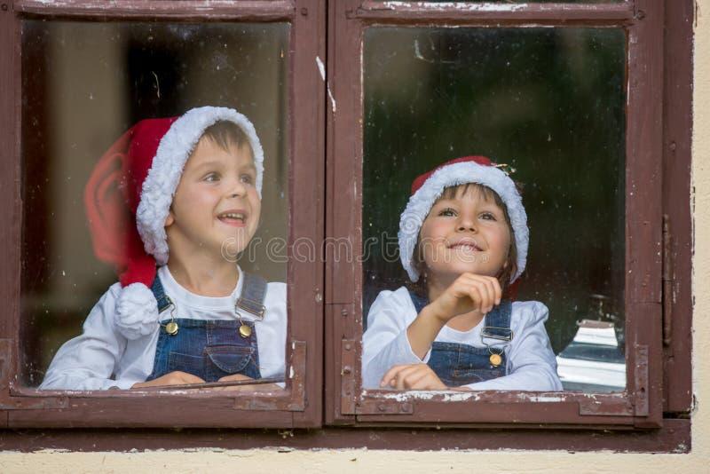 Dos muchachos lindos, hermanos, mirando a través de una ventana, para S que espera imágenes de archivo libres de regalías