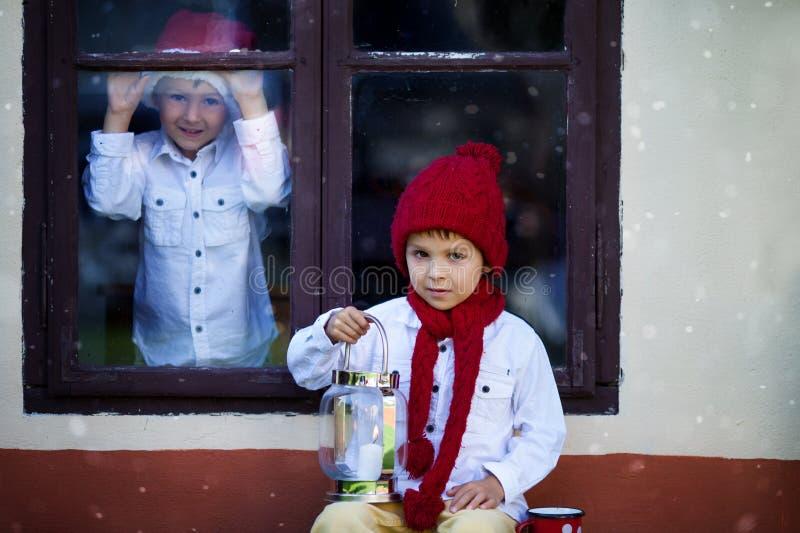 Dos muchachos lindos, hermanos, mirando a través de una ventana, para S que espera fotos de archivo libres de regalías