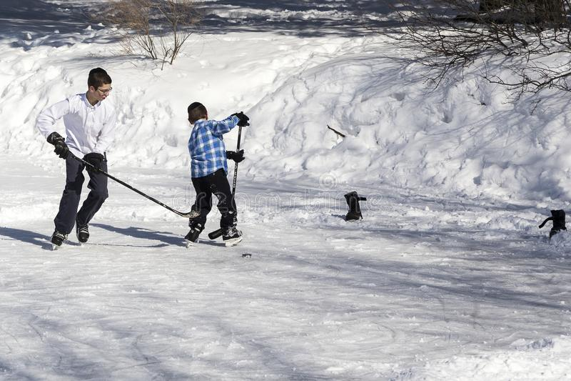 Dos muchachos ortodoxos del judío del hasidim que juegan a hockey en el hielo imagen de archivo libre de regalías