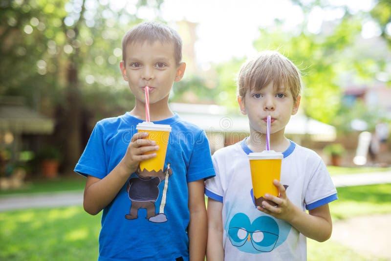 Dos muchachos que beben el cacao de las tazas de papel con la paja en parque fotos de archivo