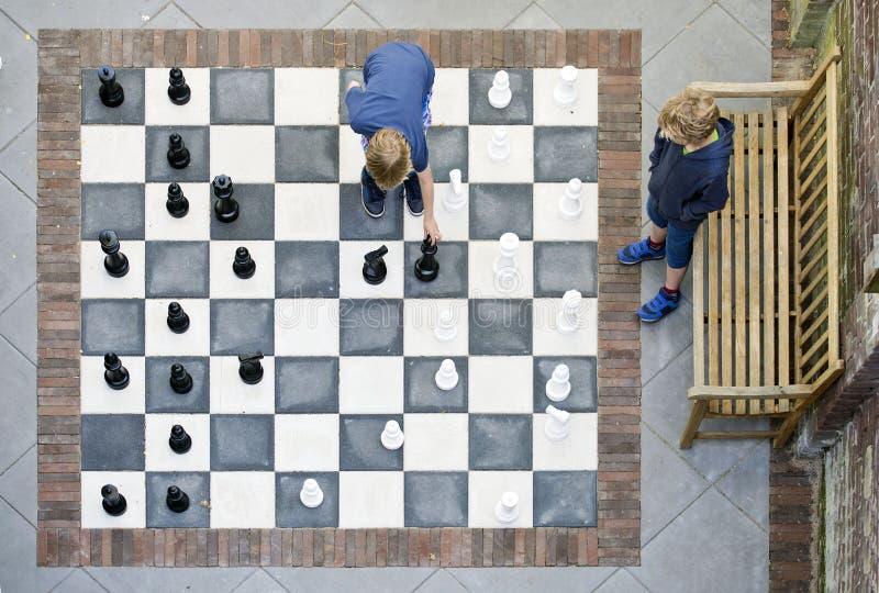 Dos muchachos que juegan a ajedrez al aire libre fotografía de archivo