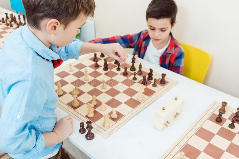 Dos muchachos que juegan a ajedrez en el torneo como deporte foto de archivo