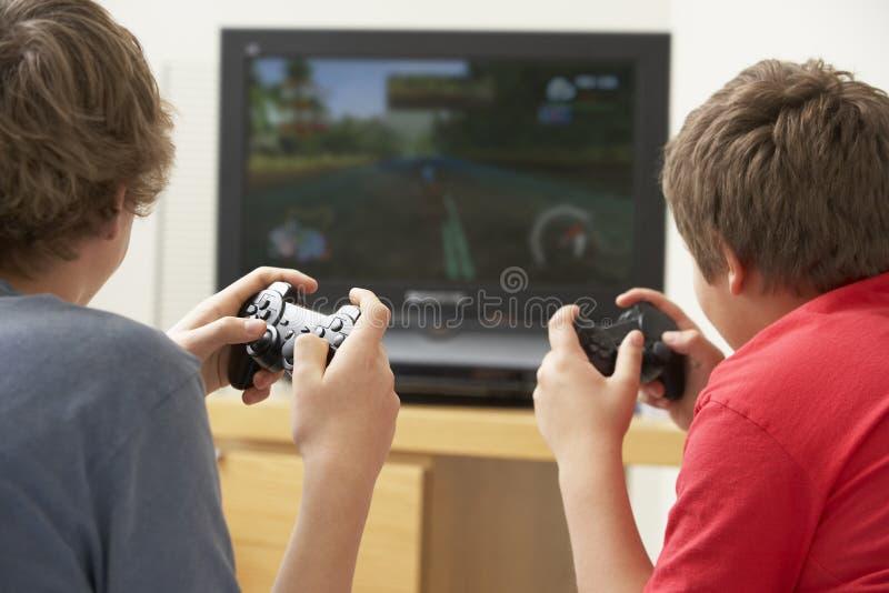 Dos muchachos que juegan con la consola del juego foto de archivo libre de regalías