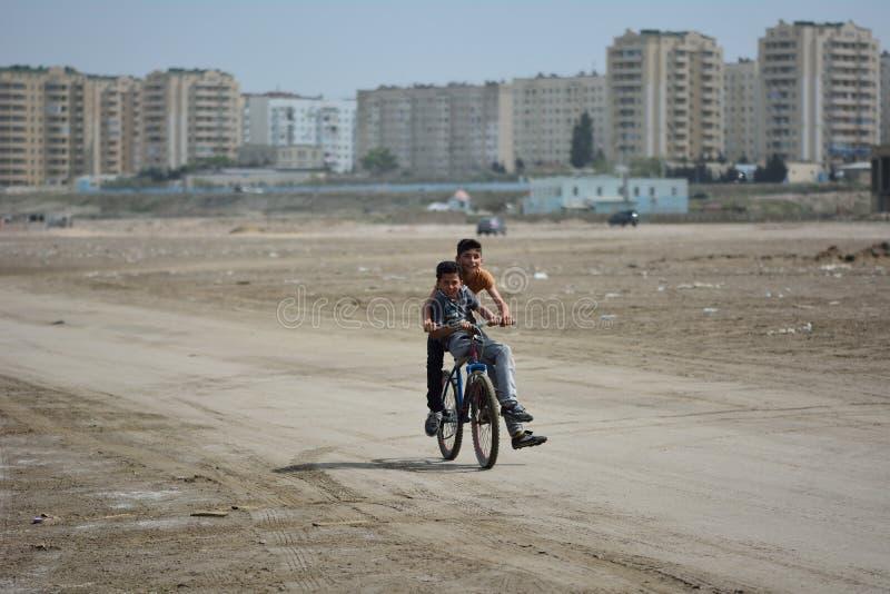 Dos muchachos que montan una bici en la playa en Sumgait, Azerbaijan foto de archivo