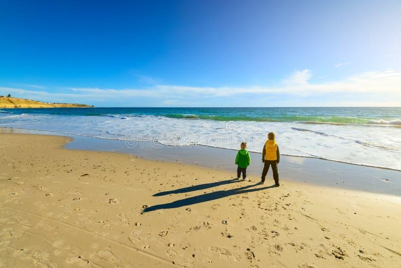 Dos muchachos que se colocan en la playa imagenes de archivo