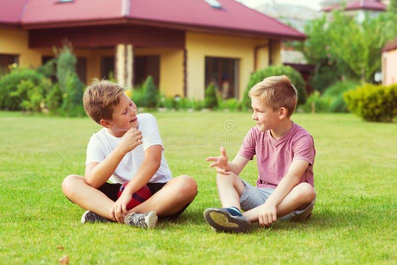 Dos muchachos que se divierten durante jugar a fútbol en patio foto de archivo libre de regalías