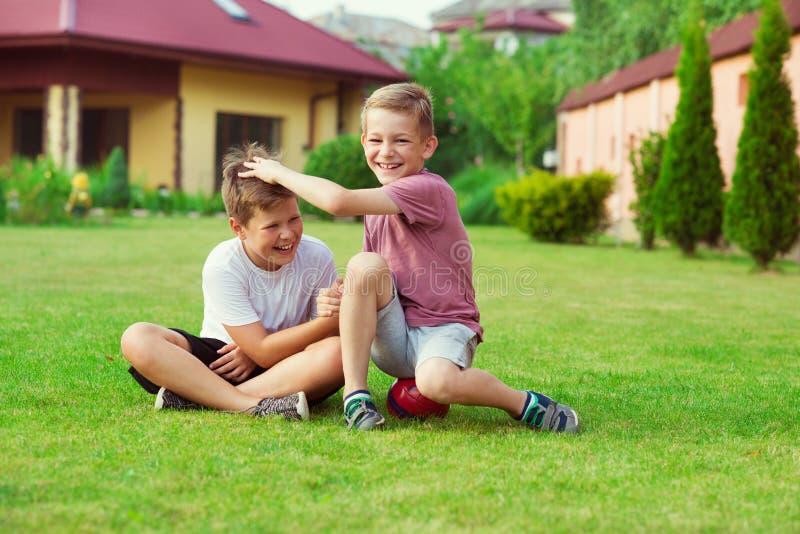 Dos muchachos que se divierten durante jugar a fútbol en patio fotos de archivo