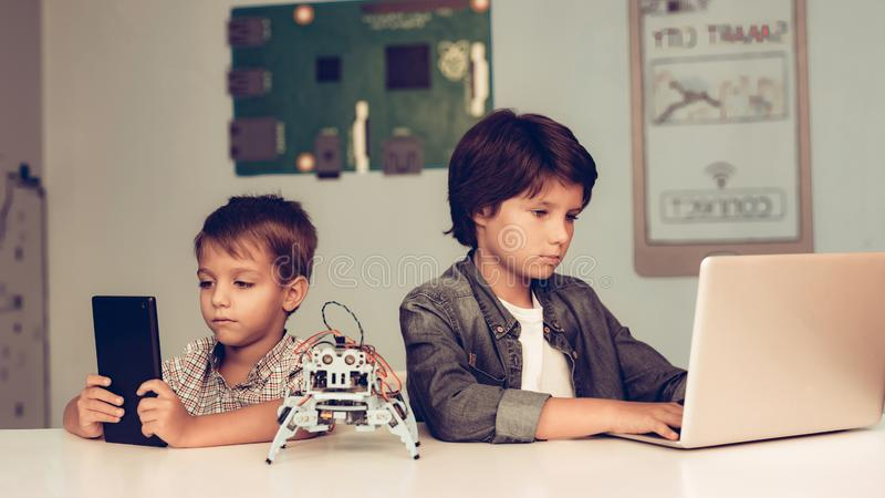 Dos muchachos que se sientan en la tabla y el robot de programación fotografía de archivo libre de regalías