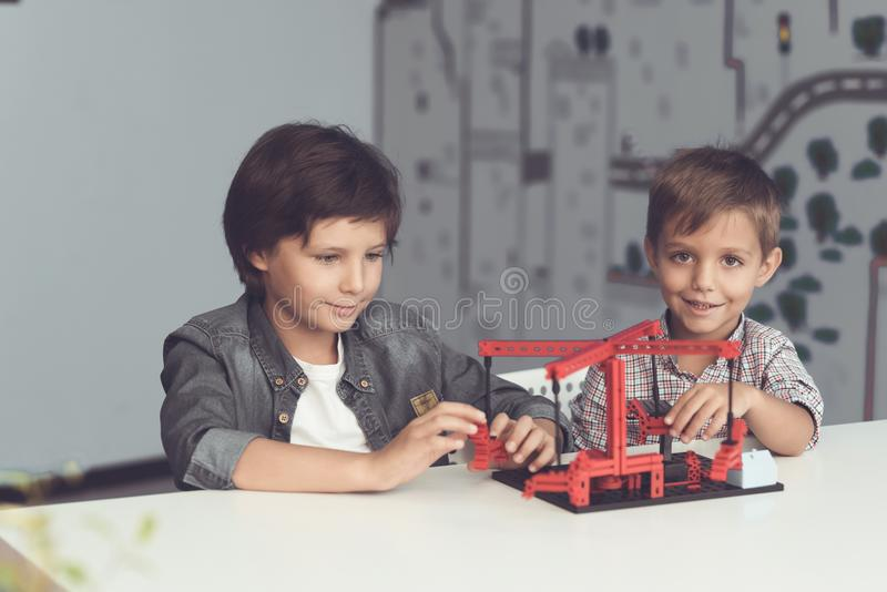 Dos muchachos se sientan en un taller en una tabla gris y crean un tiovivo imágenes de archivo libres de regalías