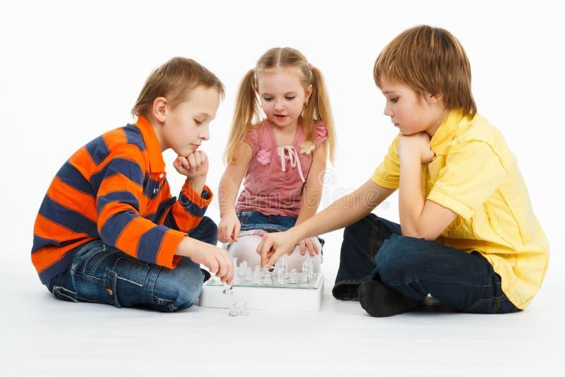 Dos muchachos y muchacha bonita que juegan a ajedrez imagenes de archivo