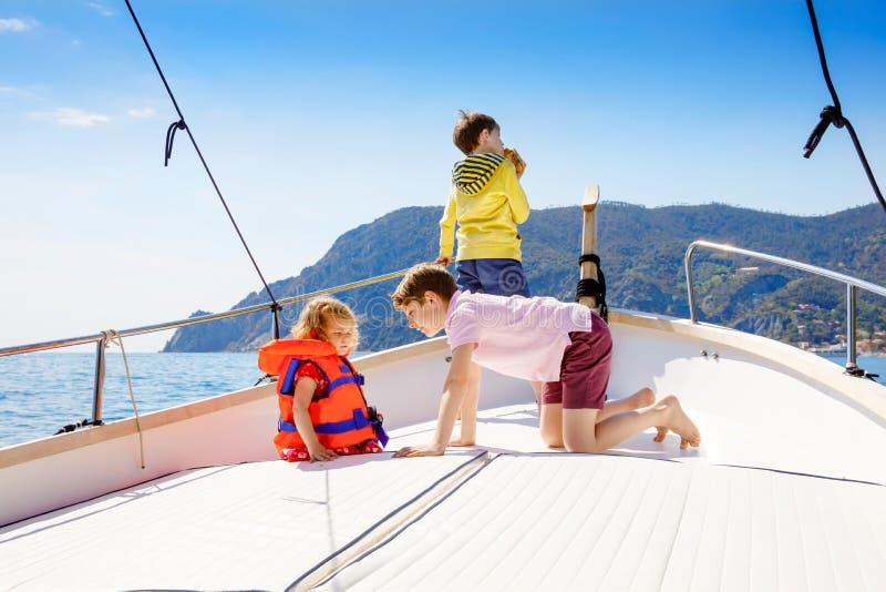 Dos muchachos y niña pequeña del niño que disfrutan de viaje del barco de navegación Vacaciones de familia en el oc?ano o el mar  imagen de archivo