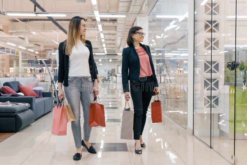 Dos mujeres adultas con los bolsos de compras que caminan en la alameda, mujeres que sonríen y que miran el escaparate foto de archivo libre de regalías
