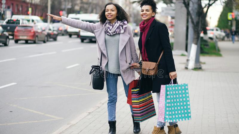 Dos mujeres afroamericanas atractivas con los panieres que piden taxi mientras que se vuelve de ventas de la alameda foto de archivo