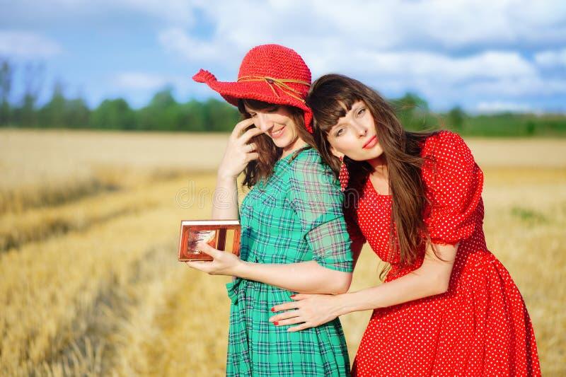 Dos mujeres alegres en un campo de trigo en la puesta del sol en un vestido largo azul y rojo del aire imagen de archivo