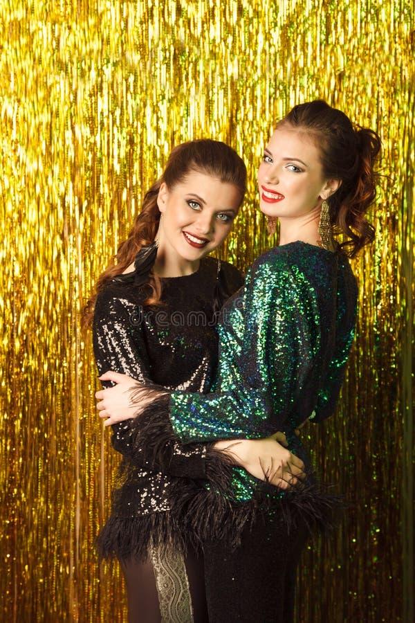 Dos mujeres alegres hermosas en el partido en backgroun chispeante fotos de archivo