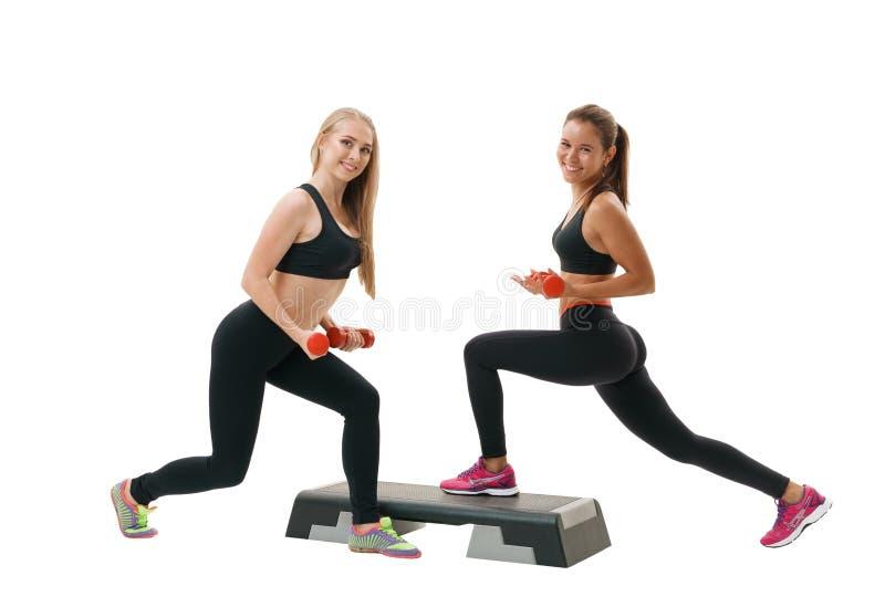 Dos mujeres aptas que ejercitan en la clase de los paso-aeróbicos fotos de archivo