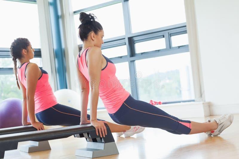 Dos mujeres aptas que realizan aeróbicos del paso ejercitan en gimnasio imagen de archivo