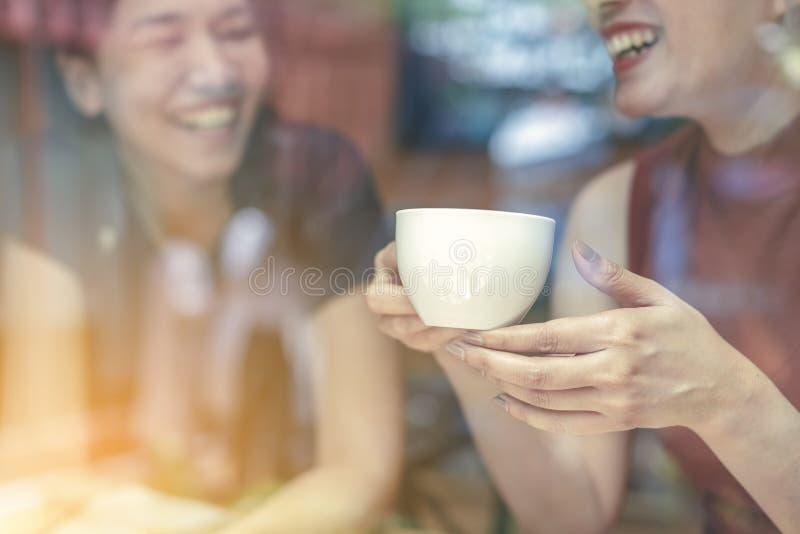 Dos mujeres asiáticas, amigos que comen un café de consumición del tiempo libre en el café Amigos que ríen junto mientras que beb foto de archivo