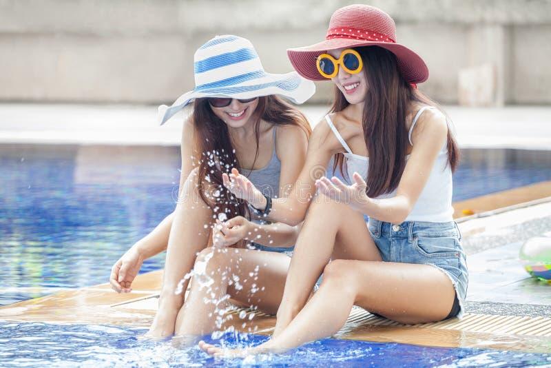 dos mujeres asiáticas jovenes hermosas en sombrero grande y las gafas de sol del verano que se sientan al borde de la piscina con imagen de archivo