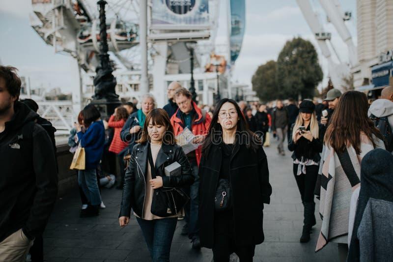 Dos mujeres asiáticas jovenes que caminan dentro de la muchedumbre a través del paseo de la reina, en un día soleado en Londres,  fotografía de archivo