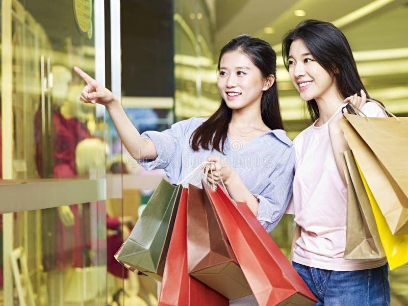 Dos mujeres asiáticas jovenes que hacen compras en alameda imagen de archivo