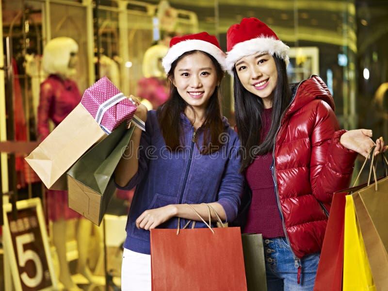 Dos mujeres asiáticas jovenes que hacen compras para la Navidad foto de archivo libre de regalías