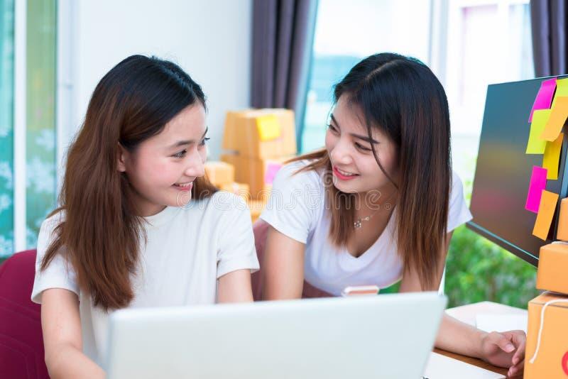 Dos mujeres asi?ticas de la amistad que miran junto al usar el ordenador port?til para en la l?nea compras y m?rketing o vendiend fotos de archivo libres de regalías