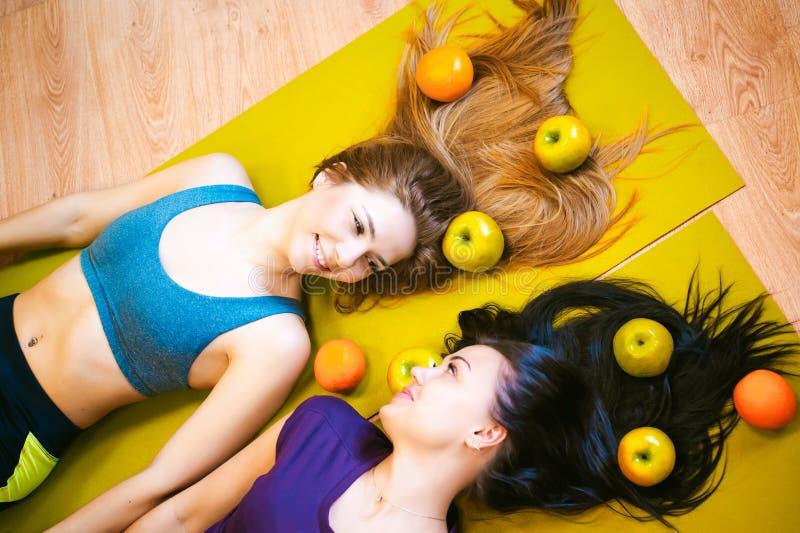 Dos mujeres atléticas jovenes de la constitución en gimnasio mienten en el piso en las esteras de la yoga fotografía de archivo