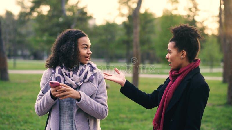 Dos mujeres atractivas de la raza mixta surpisely tienen reunión en el parque cerca de tienda de la alameda imagenes de archivo