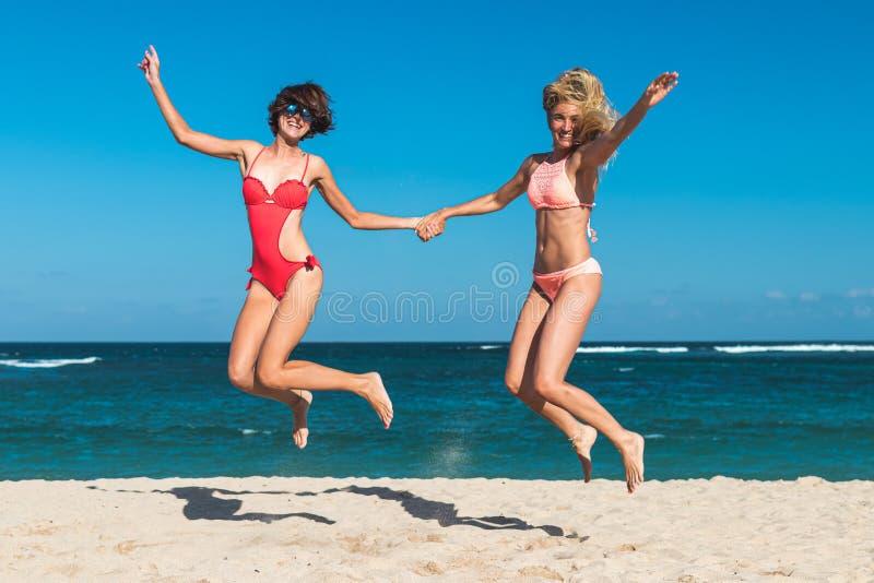 Dos mujeres atractivas jovenes están saltando en la playa y se están divirtiendo durante vacaciones en la isla de Bali fotografía de archivo libre de regalías